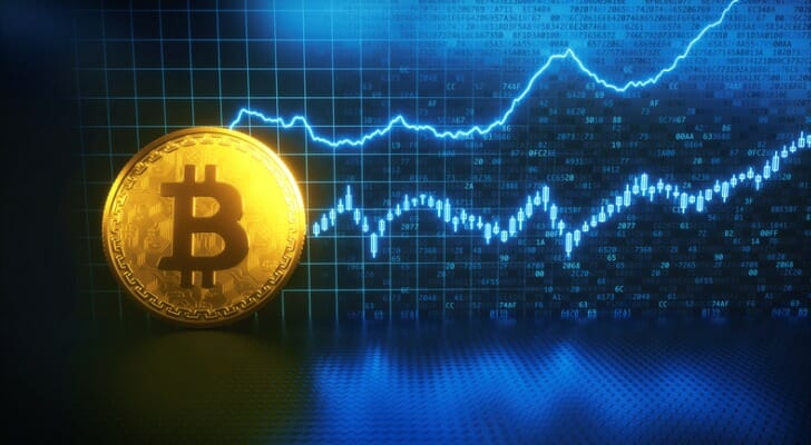 Image shows a Bitcoin gold coin with performance graphs in the background. If you own Bitcoin, you can use a cold storage wallet to store it offline, which keeps it safe from hacking and other web attacks.