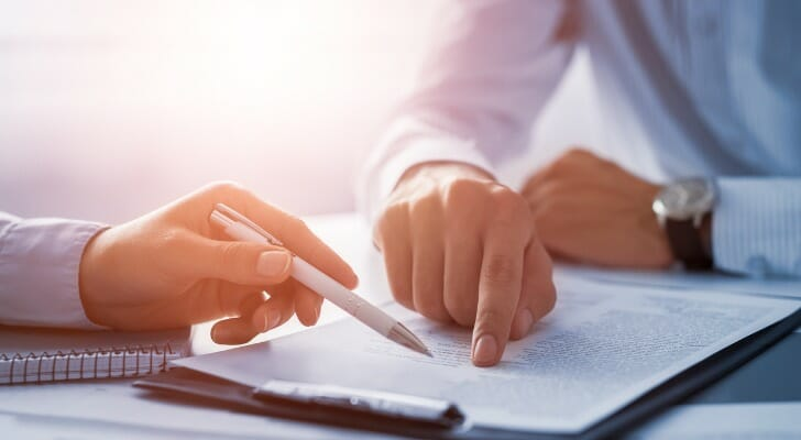 Image shows two people reviewing a written contract that sits on a desk between them. Asking the right questions and being clear about fees and services is important when hiring a financial advisor.
