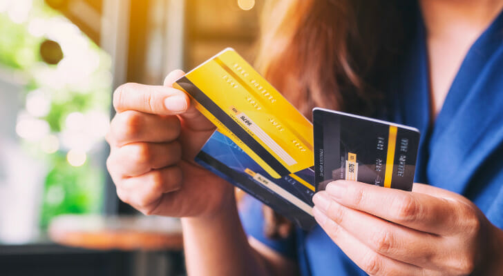 Image shows a person holding three credit cards and choosing one of them to make a purchase. SmartAsset analyzed data to conduct its latest study on the best places to get out of credit card debt.
