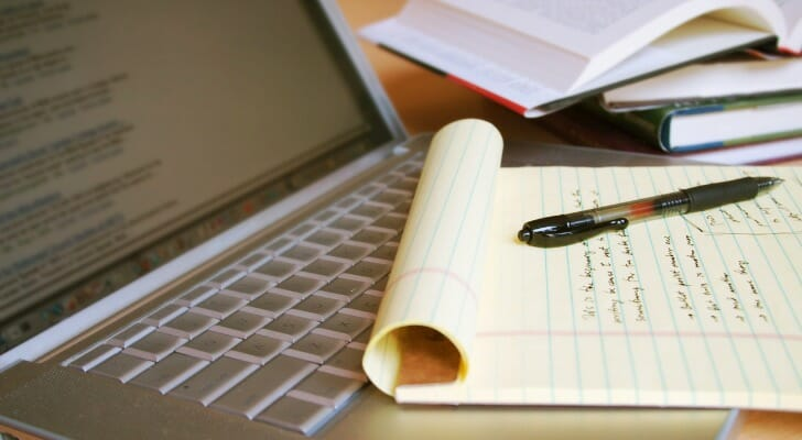 Image shows a laptop as well as a notepad with research notes written on it. Thorough research is important to complete when hiring a financial advisor.