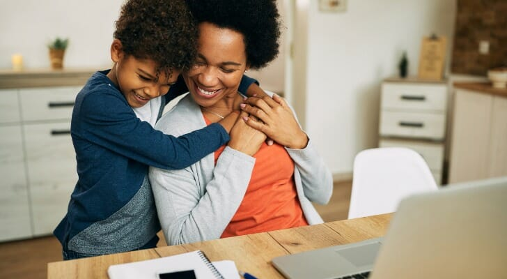 Boy with mother in her home office