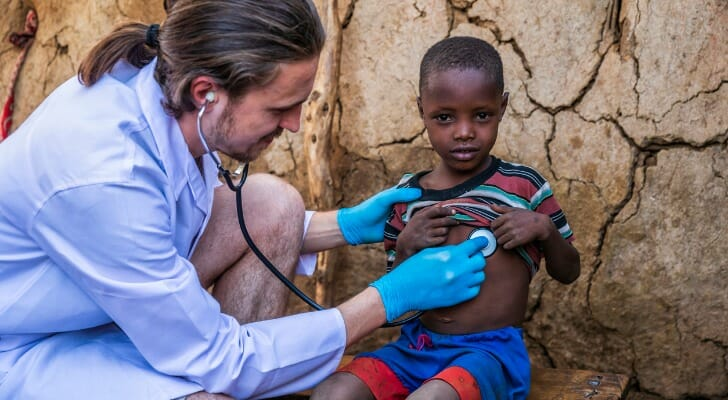 Medical worker checks the heartbeat of a small, impoverished child