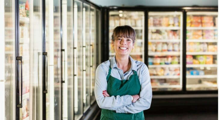 Grocery store employee standing in the freezed food section