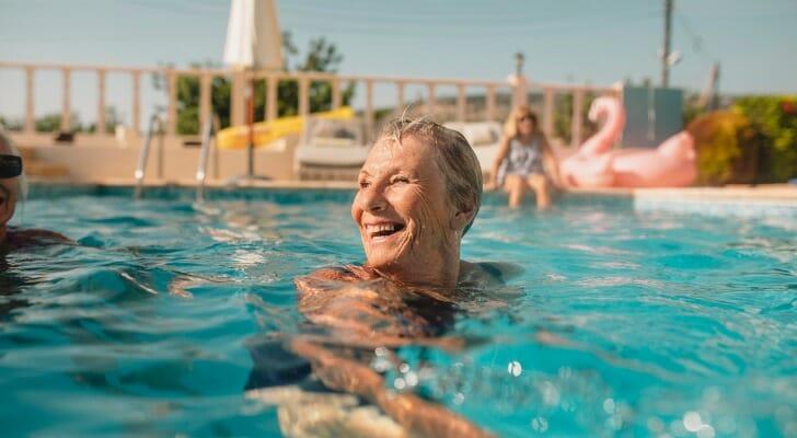 Senior woman enjoying a swim in a pool on a sunny day.