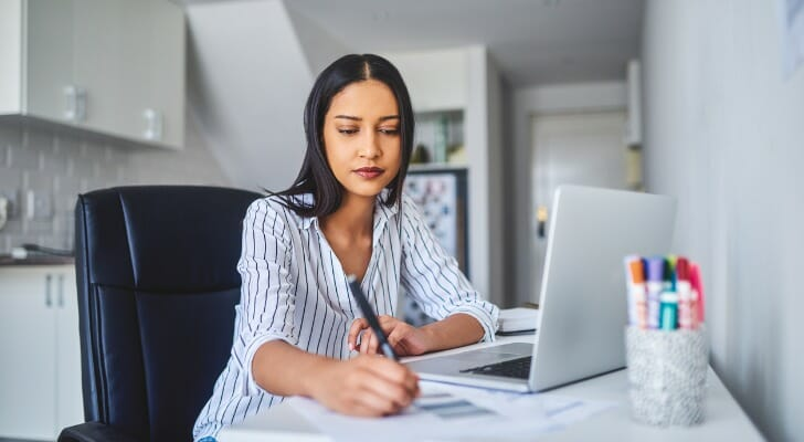 Image shows a young professional sitting in front of a laptop and taking notes for a work assignment. SmartAsset analyzed data from various sources to conduct this year's study on the best cities for young professionals.