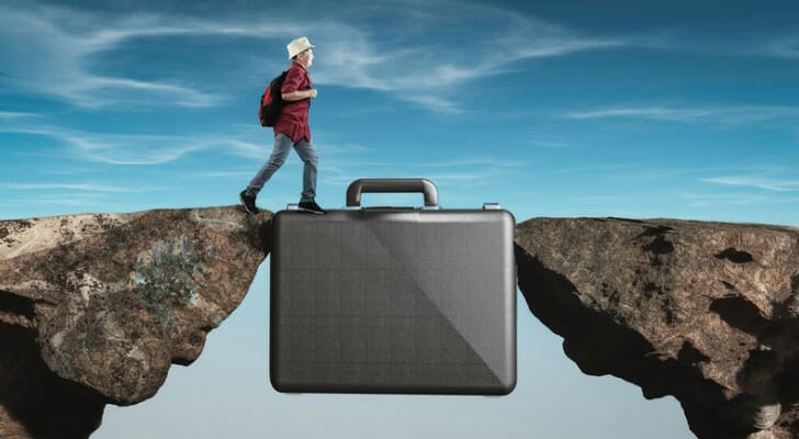 Student crossing from one precipice to another by walking on a briefcase