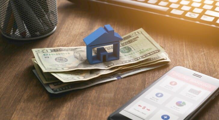 Image shows a blue house figurine on top of a stack of a few bills; these sit on a desk, next to a smartphone that shows the interface of a budgeting app. SmartAsset analyzed Census data to conduct this study on the hours of work needed to pay rent in the 25 largest U.S. cities.