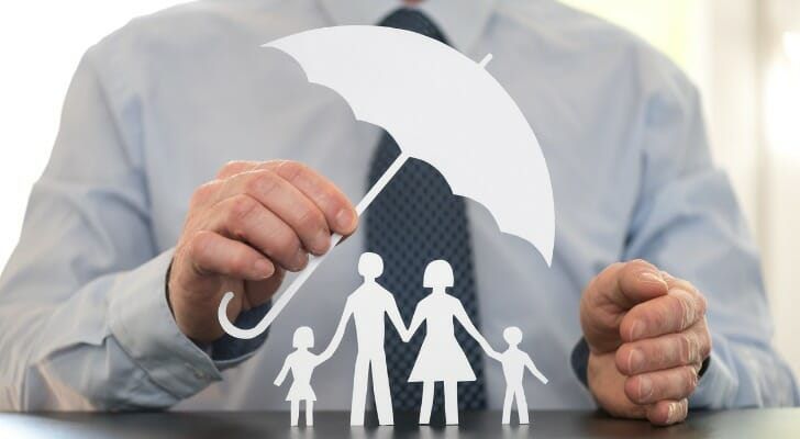 Man holds tiny model umbrella over stick figures representing a family