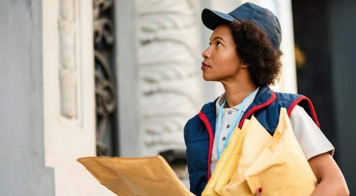 Image shows a woman who works as a courier holding several large envelopes at a delivery address. SmartAsset used BLS data to conduct this year's study on the fastest-growing jobs for women.