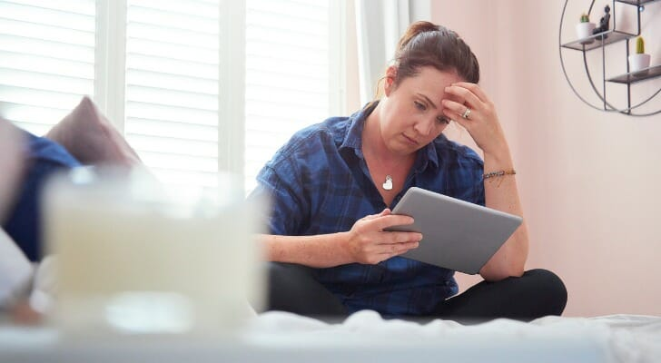 Image shows a person wearing a navy blue shirt and black pants sitting on a bed holding a tablet and rubbing their forehead as they look at their financial information. This study by SmartAsset finds the U.S. cities with the most financial stress.