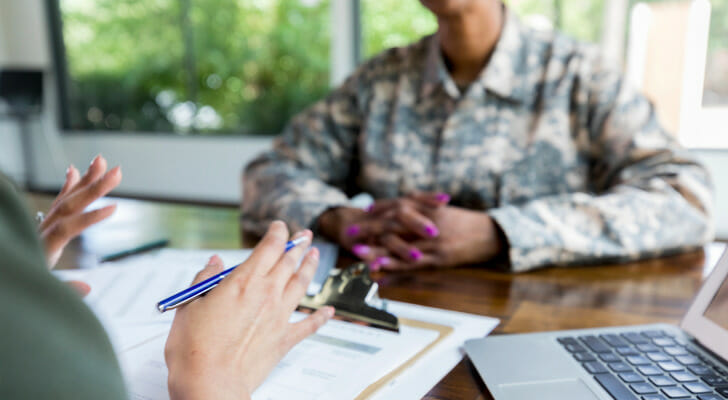 Image shows an advisor sitting across from a member of military personnel; there are official papers and a computer on the desk between them. In this study, SmartAsset analyzed various data points to find the best states for veterans.