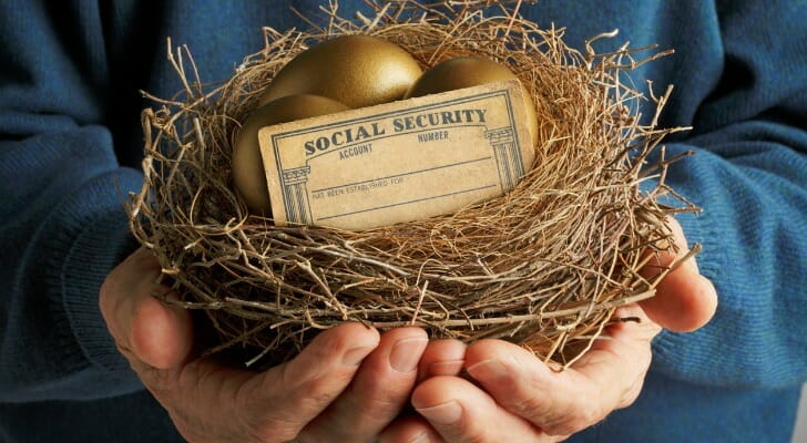 Man holding a bird's nest with a Social Security card and gold egg in it