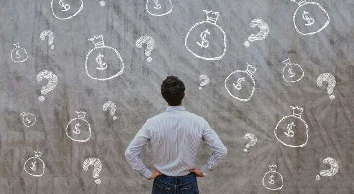 Man standing in front of chalkboard with drawings of money bags and question marks