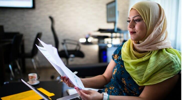 Muslim woman checks her investment returns