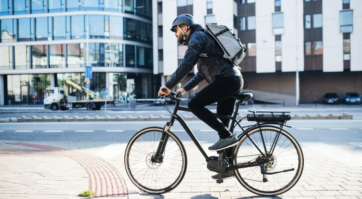 A bicyclist wearing a helmet rides on a city street. SmartAsset analyzed various data sources to identify the most bike-friendly cities in the U.S.