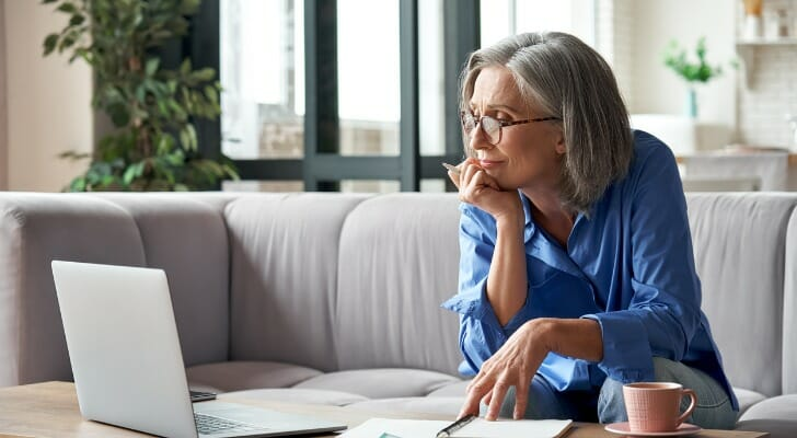 Image shows a retired individual looking at a laptop and paperwork to review their retirement benefits. SmartAsset conducted a study on the prevalence of employer-sponsored retirement plans in the U.S.