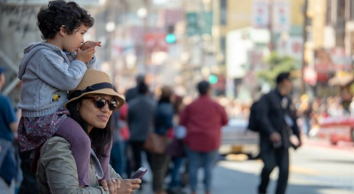 Image shows a parent and child at a parade outside. SmartAsset analyzed various data sources to conduct its study on where Hispanic and Latino Americans fare best economically.