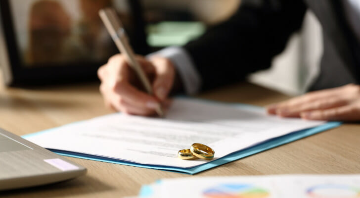 Image shows a person signing divorce documents. 2021 SmartAsset Study: Where Divorces Are Becoming More Common