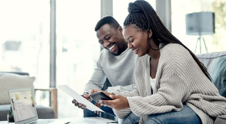 A couple checks on their investments together. Research from Dimensional Fund Advisors points to the long-term benefits of diversification within a portfolio.