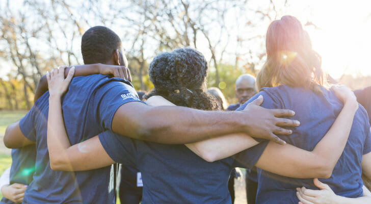 Image shows a group of volunteers huddled together at the beginning of a charity event. SmartAsset analyzed key metrics related to giving and volunteering to conduct its latest study on the places where Americans give the most to charity.