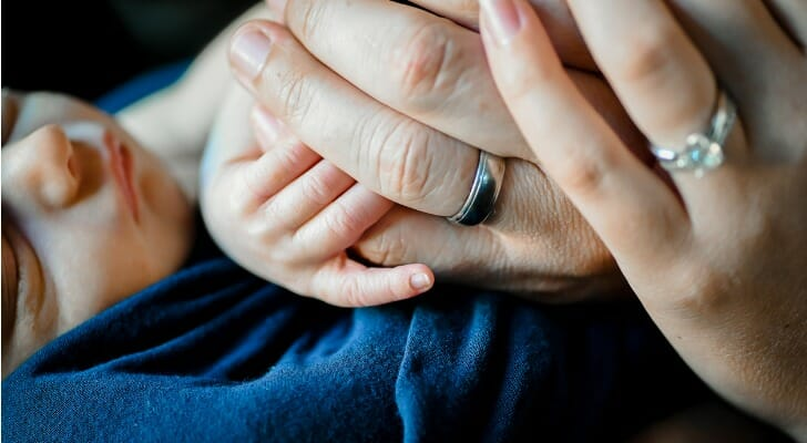 Infant holding hand of father