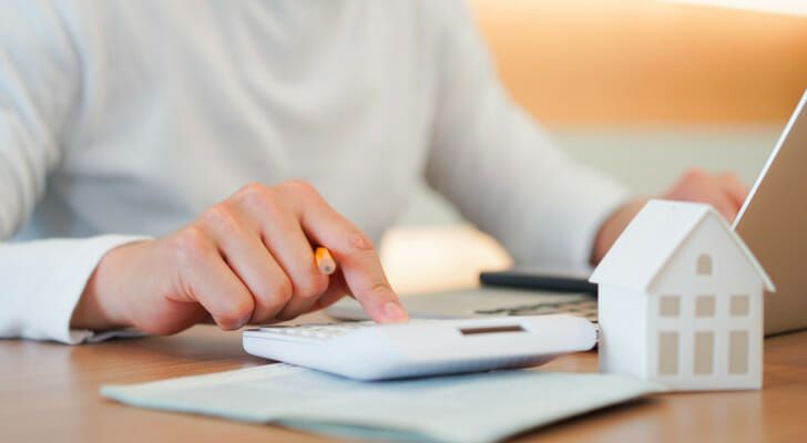Image shows a homeowner doing monthly housing cost calculations. SmartAsset analyzed Census data to conduct its 2021 study identifying where the most and fewest homeowners are severely housing cost-burdened.