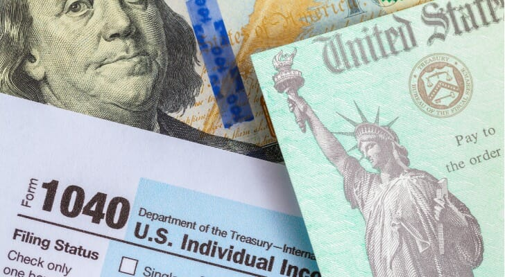 Image shows several U.S. government tax forms and documents. SmartAsset's study looks at how the Trump tax bill affected itemized deductions.