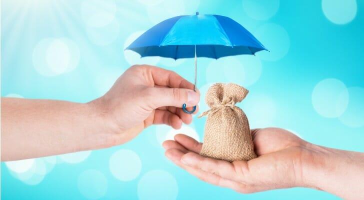 Umbrella being held over a bag of money