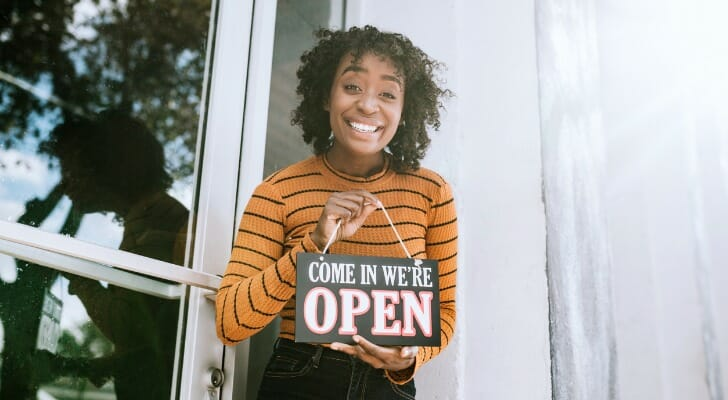 """A small business owner stands outside her shop with an """"Open"""" sign"""