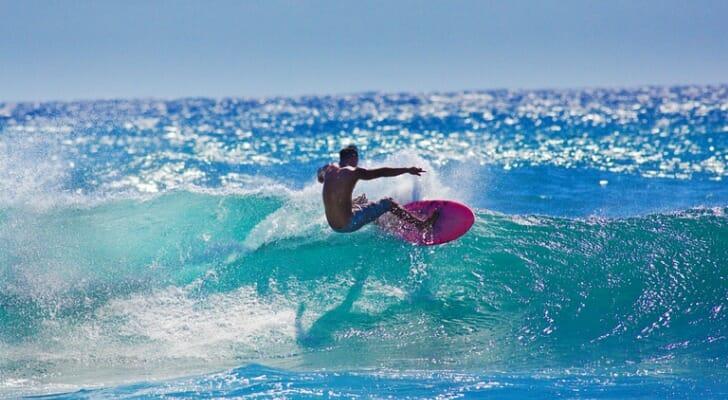 A local Hawaiian surfer surfing at Poipu Beach, Kauai, Hawaii