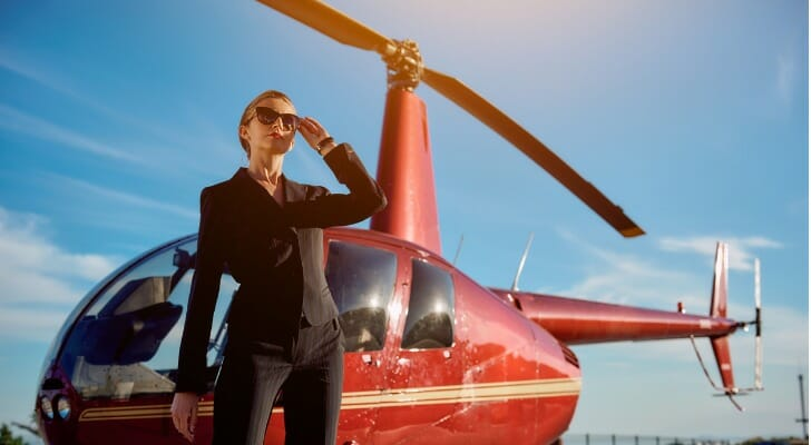 High-net-worth female next to helicopter