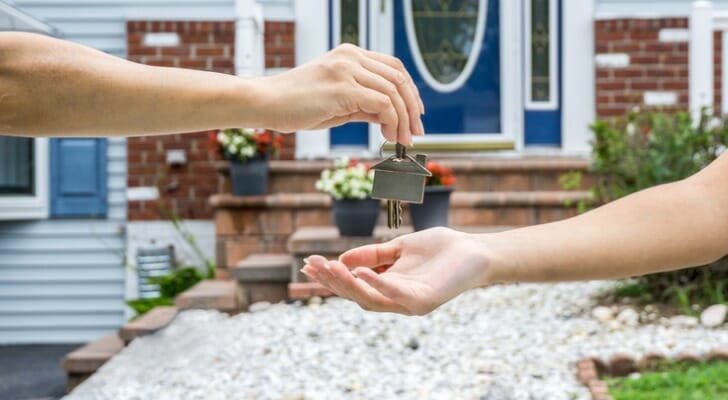 Image shows one person's hand placing the key to a new home in a second person's hand; the front porch of the new home is in the background. SmartAsset analyzed various data sources to find out how long it takes renters to become homeowners.
