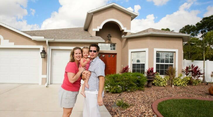 Image shows two adults with their baby in front of a large beige house with a landscaped front yard and spacious driveway. SmartAsset analyzed IRS data to conduct its study on where upper-middle-class people are moving.